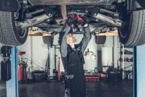 auto mechanic fixing a car in a hot garage